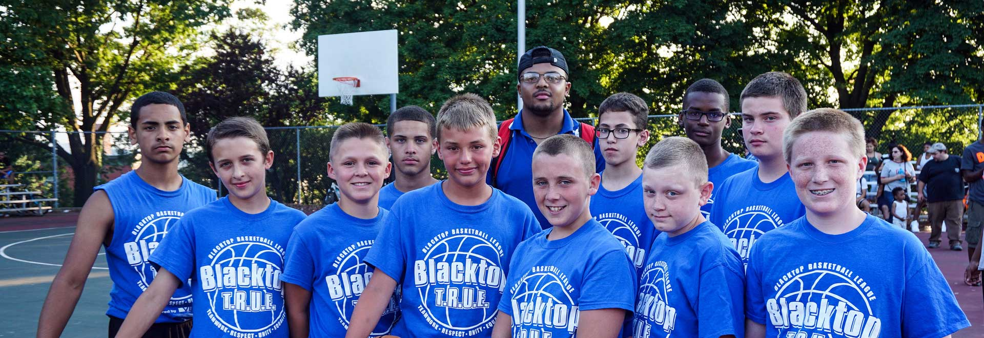 Blue team photo with coach and basketball net in background